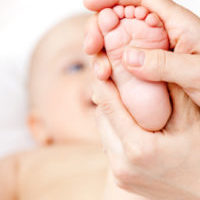 Mother massaging her child's foot, shallow focus